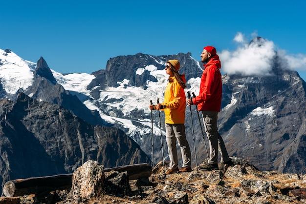 Trekking en nordic walking. jong koppel doet nordic walking in de bergen. actieve rust op de natuur. een actief stel houdt zich bezig met wandelen. een jong stel houdt zich bezig met het volgen. ruimte kopiëren