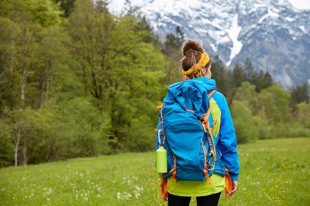 Trekking, wandelen en wandelen concept. actieve vrouw wandelaar vormt op de heuveltop, wandelt tegen het berglandschap, heeft actieve rust