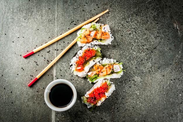 Trend hybride eten japanse aziatische keuken mini sushi-tacos broodjes met zalm hayashi wakame daikon gember rode kaviaar zwarte stenen tafel met stokjes sojasaus