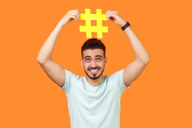 Trending en bloggen, virale inhoud. portret van een vrolijke brunette man met baard in wit t-shirt glimlachend en met een groot hashtag-teken boven het hoofd. indoor studio-opname geïsoleerd op oranje achtergrond