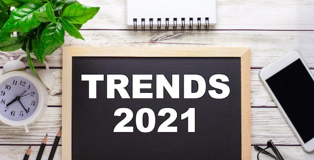 Trends 2021 geschreven op een zwarte muur in de buurt van potloden, een smartphone, een wit notitieblok en een groene plant in een pot