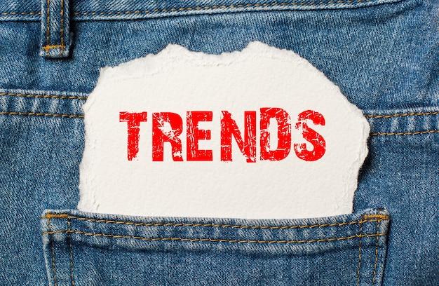 Trends op wit papier in de zak van blauwe spijkerbroek