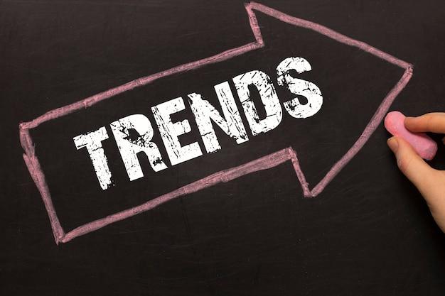 Trends - pijl met tekst en vrouwelijke hand met krijt