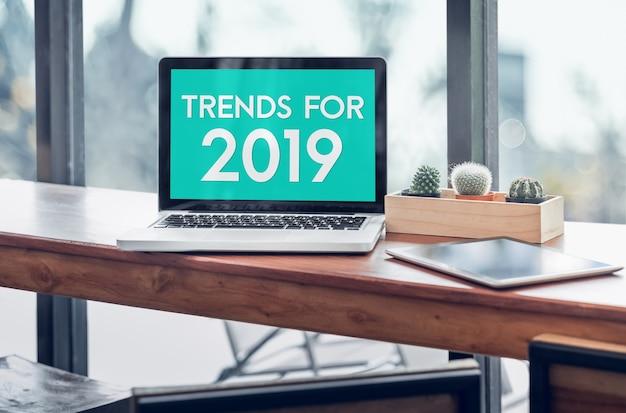 Trends voor 2019-woord in laptop het computerscherm met tablet op hout bevonden lijst