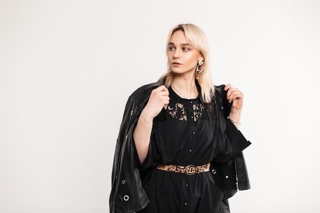 Trendy aantrekkelijke jonge vrouw blonde in stijlvolle kleding jurken modieuze leren jas. schattig prachtig meisje mannequin in vintage zwarte jurk poseren. elegante damesoutfit.