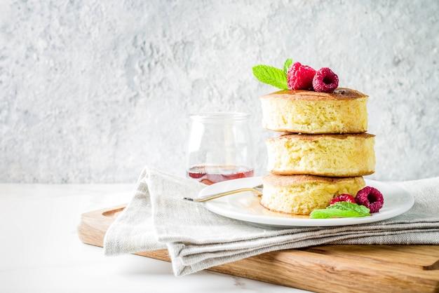 Trendy aziatisch eten, pluizige japanse soufflépannenkoeken, hotcakes met ahornsiroop en frambozen lichte betonnen tafel