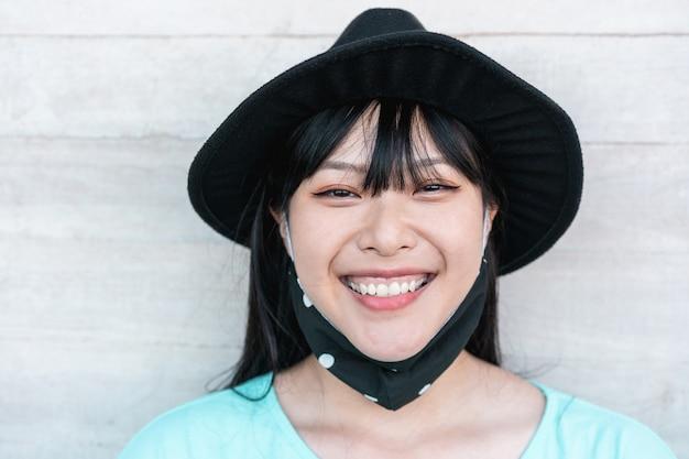 Trendy aziatisch meisje lachend terwijl het dragen van een beschermend gezichtsmasker tijdens de uitbraak van het coronavirus