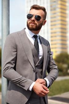 Trendy blanke man in grijze smoking of pak met fic-knop op de mouw