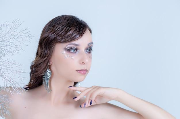 Trendy blauwe make-up. mooie jonge vrouw met handen op haar gezicht die één oog en mond behandelen. perfecte huid. nagelkunst en make-up concept. high fashion met strass, sneeuwkoningin. exemplaarruimte