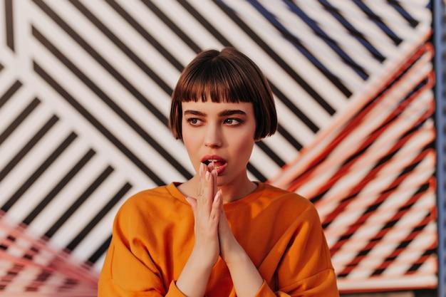 Trendy brunette vrouw in oranje stijlvolle sweater die wegkijkt in café
