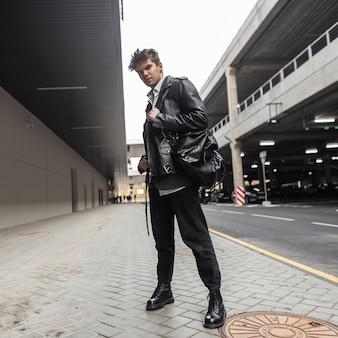 Trendy coole jongeman in een stijlvolle leren zwarte jas in een shirt in spijkerbroek in laarzen met een mode-rugzak met een kapsel dat zich voordeed in de buurt van de weg in de stad. urban guy hipster staat op straat.
