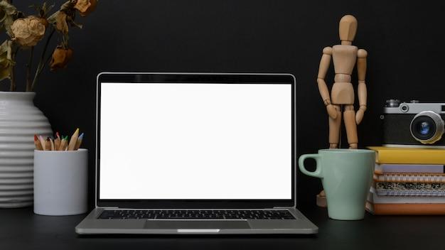 Trendy designer werkplek met leeg scherm laptop op zwarte tafel met donkere muur