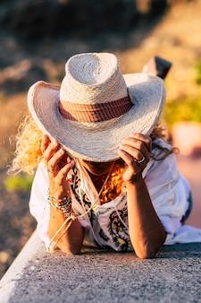 Trendy en mode vrouw met zomer mooie hoed op zonnige dag - vrijetijdsbesteding in de buitenlucht voor meisje met verborgen gezicht - onherkenbare mensen genieten van de zomer