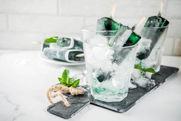 Trendy eten, aziatische vegan desserts, zelfgemaakte ijsijslollys met algenspirulina, geserveerd met munt in glazen met ijs,