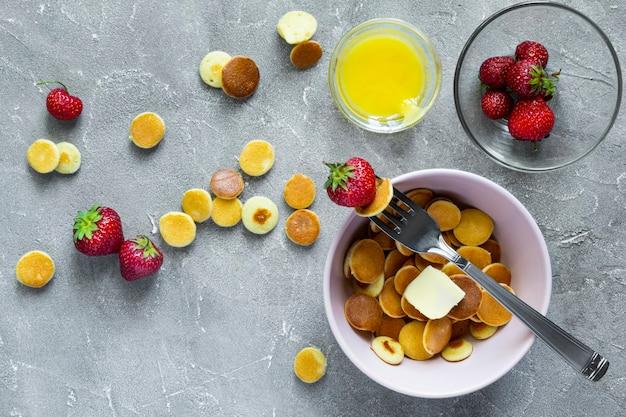 Trendy eten - pannenkoekgraangewas. hoopje mini ontbijtgranen pannenkoeken met aardbeien en yoghurt in lichte boul. bovenaanzicht of plat leggen.
