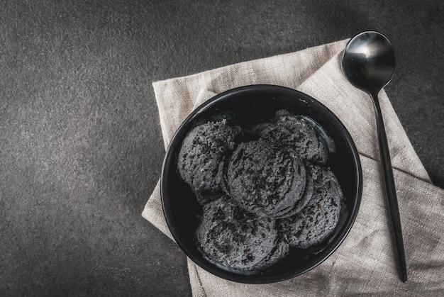 Trendy eten. zwart ijs met zwarte sesam, in een zwarte kom op een zwarte stenen tafel, met een lepel.