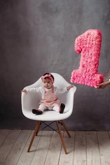 Trendy gekleed babymeisje in hoofdband en kledingzitting op witte stoel. ze heeft een jubileum