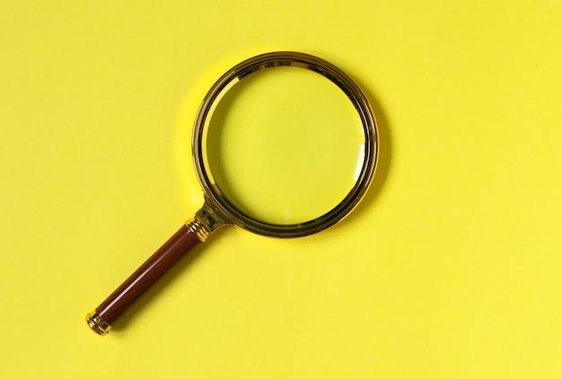 Trendy gekleurde gele achtergrond met vergrootglas
