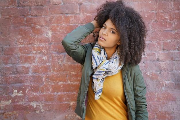 Trendy gemengd ras uitgevoerd meisje staande door bakstenen muur
