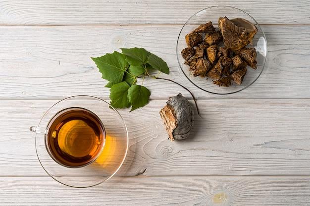 Trendy gezonde koffie met chaga-paddenstoelen. droge paddenstoelen en berkentakken. kopieer ruimte, bovenaanzicht.