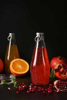 Trendy granaatappel en oranje drankje met basilicum zaden in flessen op zwarte ondergrond, verticaal formaat