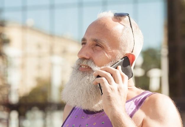 Trendy hogere mens die smartphone in centrum van de binnenstad gebruiken openlucht - rijp maniermannetje die pret met nieuwe tendenstechnologie hebben - technologie en blij bejaard levensstijlconcept