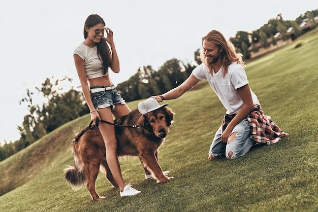 Trendy hond. knappe jonge man die een hoed op de hond zet terwijl hij zorgeloze tijd doorbrengt met zijn vriendin buitenshuis