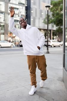 Trendy hoodie op man met bruine broek in de stad