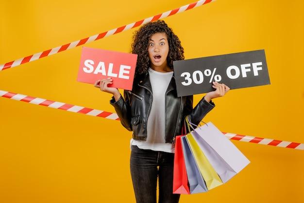 Trendy jong zwart meisje met verkoop 30% teken en kleurrijke boodschappentassen geïsoleerd over geel met signaalband