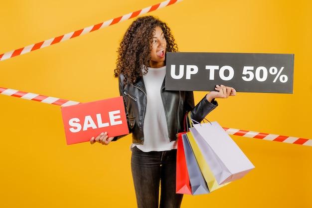 Trendy jong zwart meisje met verkoop 50% teken en kleurrijke boodschappentassen geïsoleerd over geel met signaalband