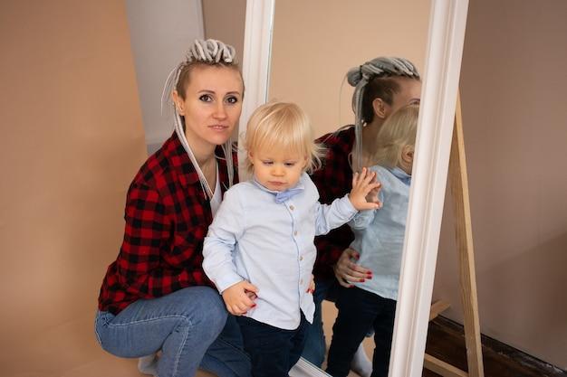 Trendy jonge hipster vrouw met dreadlocks moeder met kleine jongen op beige muur