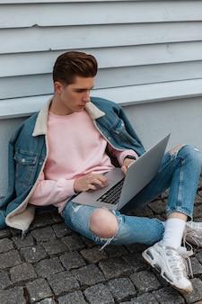 Trendy jonge man in roze sweatshirt in casual modieuze spijkerbroek kleding werkt op afstand op laptop zittend op stenen tegels buitenshuis. succesvolle moderne blogger werkt op internet in de stad.