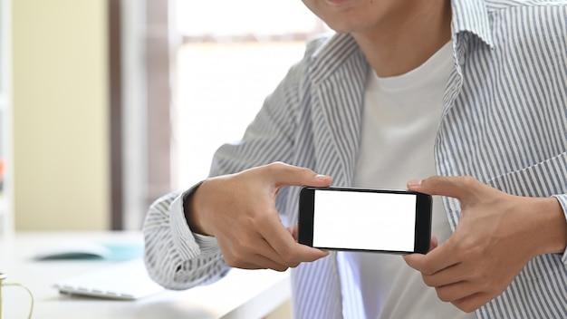Trendy jonge man met leeg scherm van zijn mobiele telefoon