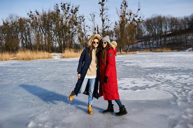 Trendy jonge meisjes lopen en hebben plezier in de winter in de buitenlucht