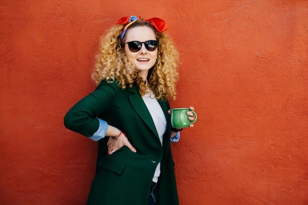 Trendy jonge mooie vrouw met pluizig blond haar dat hoofdband, zonnebril en jas draagt.