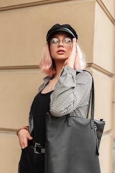 Trendy jonge schoonheidsvrouw met bril en een vintage hoed in een modieus geruit hemd met een stijlvolle leren tas staat in de buurt van de muur in de stad. urban vrouwelijke herfststijl look outfit