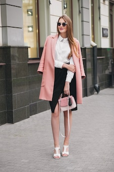 Trendy jonge stijlvolle mooie vrouw die in de straat loopt, roze jas draagt, tas, zonnebril, wit overhemd, zwarte rok, mode-outfit, herfsttrend, glimlachend gelukkig, accessoires