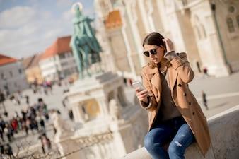 Trendy jonge vrouw buiten zitten en het gebruik van de mobiele telefoon