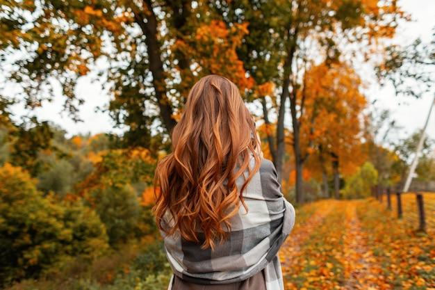 Trendy jonge vrouw in stijlvolle herfstkleren geniet van het herfstlandschap in het park. elegant meisjesmodel in een modieuze jas in een gebreide vintage sjaal staat in het bos. uitzicht vanaf de achterkant.