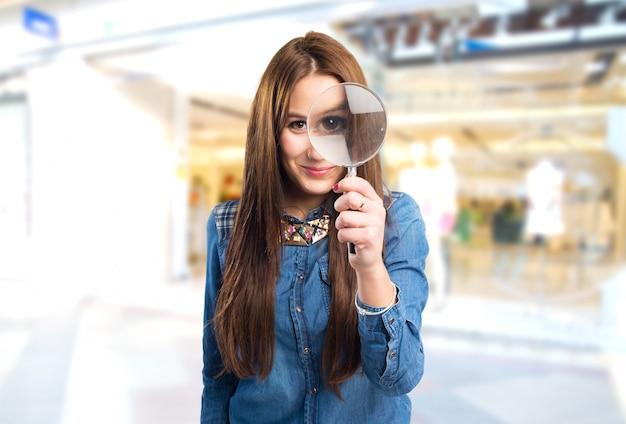 Trendy jonge vrouw met een vergrootglas in de voorkant van haar oog