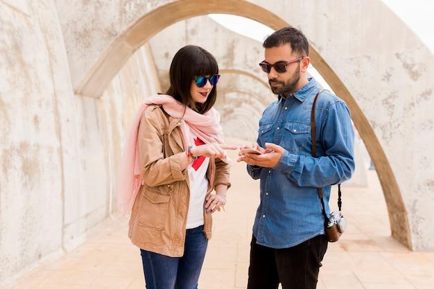 Trendy jonge vrouw wijzende vinger naar mobiele telefoon