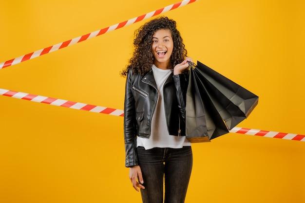 Trendy jonge zwarte die jasje met document het winkelen zakken draagt die over geel met signaalband worden geïsoleerd