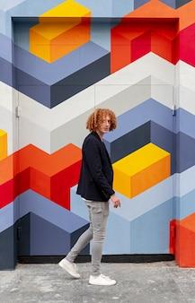 Trendy kerel die dichtbij kleurrijke muur loopt