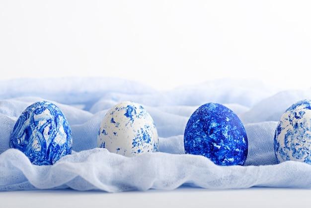 Trendy klassieke blauwe eieren van pasen in rij op lichtblauw servet op witte achtergrond