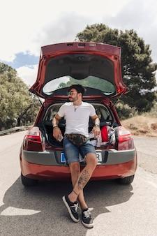 Trendy knappe jonge man met een tatoeage leunend op de auto kofferbak
