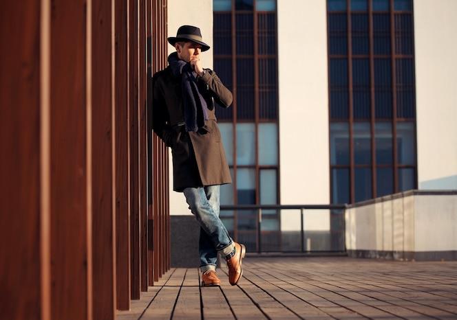 Trendy knappe jongeman in herfst mode staande in stedelijke omgeving.