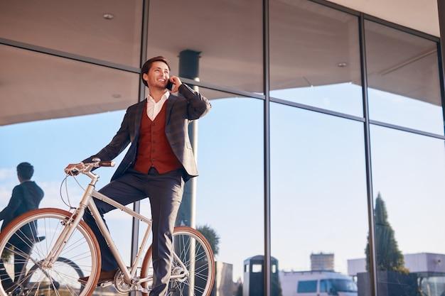 Trendy lachende zakenman praten over telefoon zittend op de fiets
