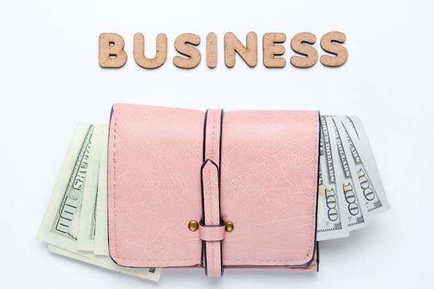 Trendy lederen portemonnee met dollarbiljetten op wit oppervlak met tekst bedrijf.