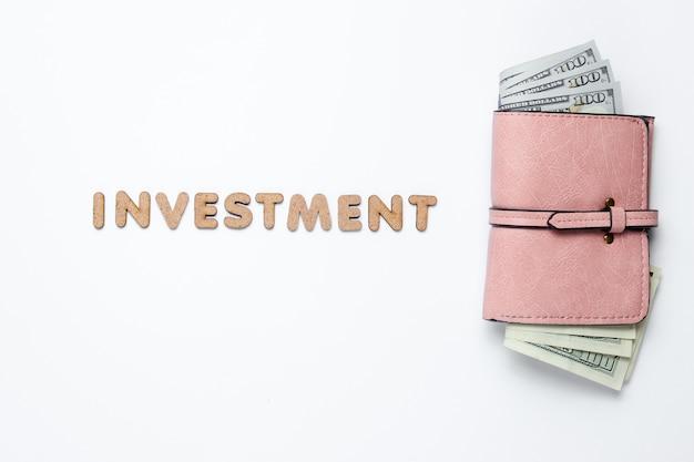 Trendy lederen portemonnee met dollarbiljetten op wit oppervlak met tekst investering.