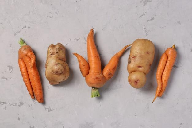 Trendy lelijke biologische aardappelen en wortelen op grijze achtergrond, lelijk voedselconcept, horizontaal formaat, bovenaanzicht